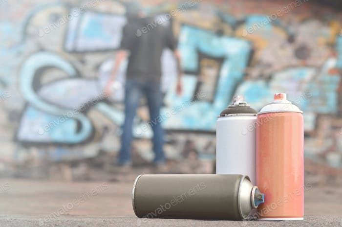 A still-life of several used paint cans of different colors against the wall