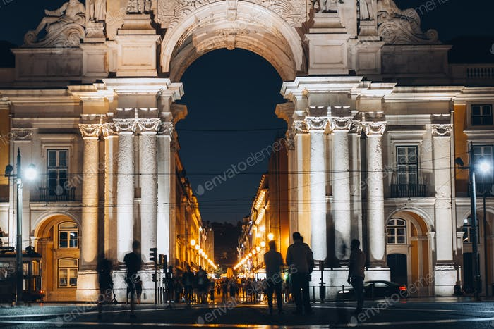 Rue Augusta arch in Commerce square at night at Praca do Comercio. Tourist people silhouette, trams