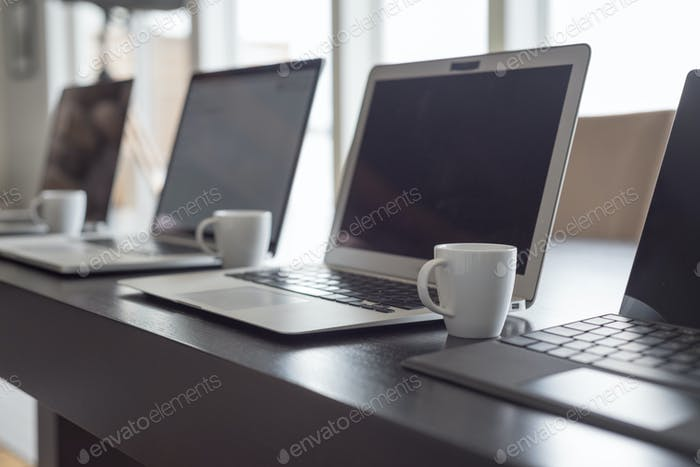 Laptop computers with coffee cups