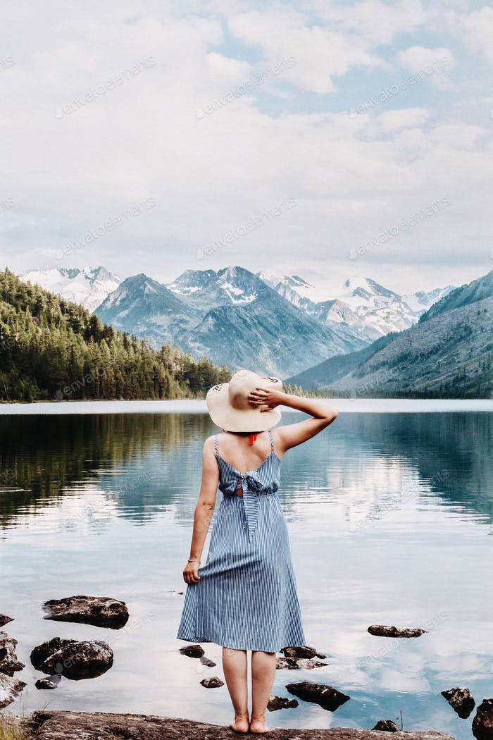 Girl stand in a dress by the lake, looking on a snowy mountains in a summer