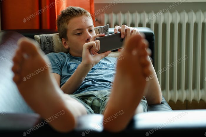 Teenager boy laying on the couch 🛋 and using mobile phone 📱.