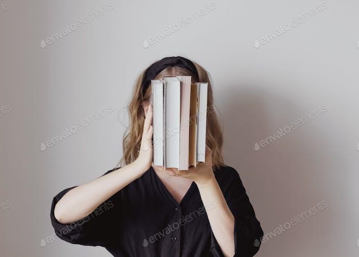 Die Frau bedeckt ihr Gesicht mit Büchern.Konzept von Lebensstil, Bildung, Information, Intelligenz und