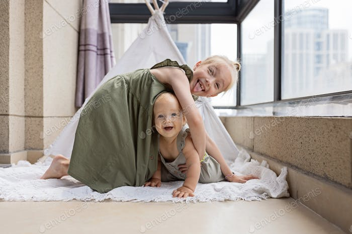 Happy caucasian siblings having fun when playing together at home on balcony in cozy wigwam
