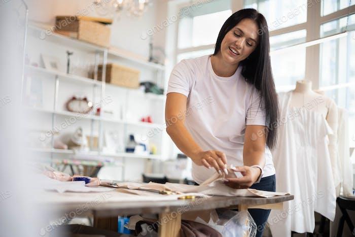 Portrait of beautiful seamstress woman posing at workplace sewing workshop enjoying small business