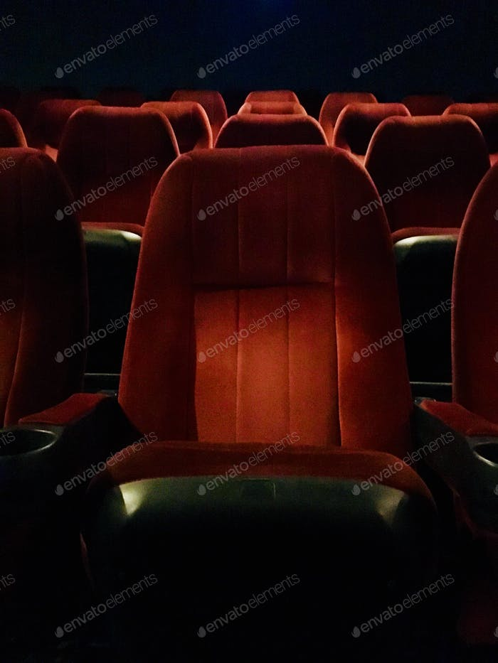 Rows of red seats at movie theatre.