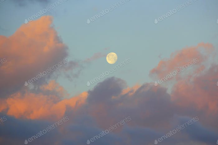 Beautiful sunrise sky reflected in the clouds with the moon setting.