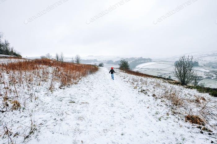 Young boy running in the snow in countryside Yorkshire, United Kingdom