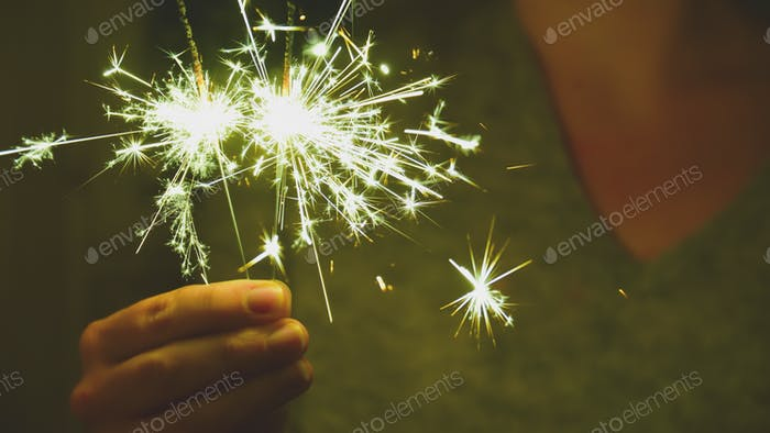 Human hands holding Festive sparklers to celebrate nye the new year