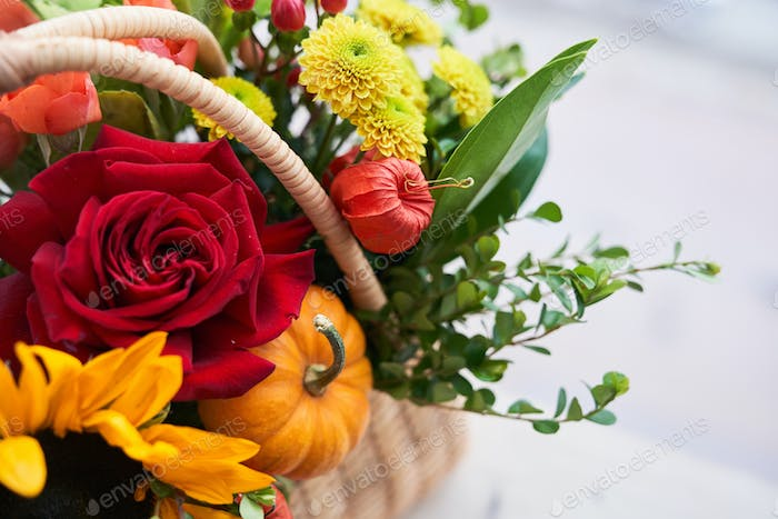 Close-up of a basket with beautiful autumn flowers made of red roses, sunflowers and green leaves