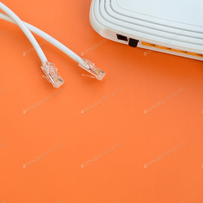 Internet router and Internet cable plugs lie on a bright orange background