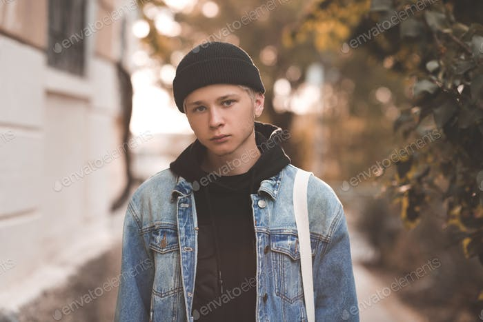 Stylish handsome teen boy 16-17 year old wearing denim jacket and knit hat over city background