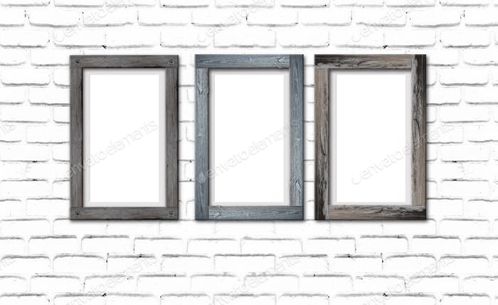 Collection of brown wood frames on brick wall. For interiors decor mockup