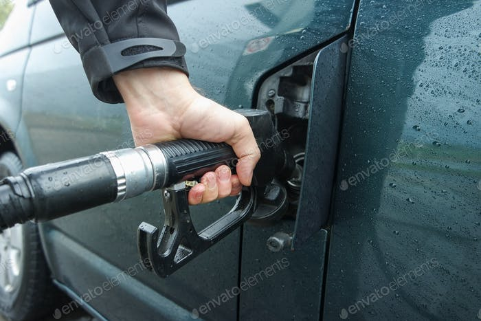 Man refueling green car at the fuel station.