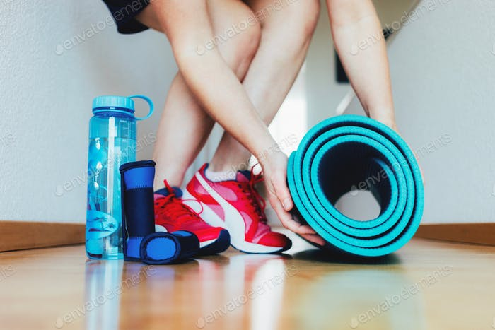 Woman preparing for workout at home with dumbbells, yoga mat and bottle of water.