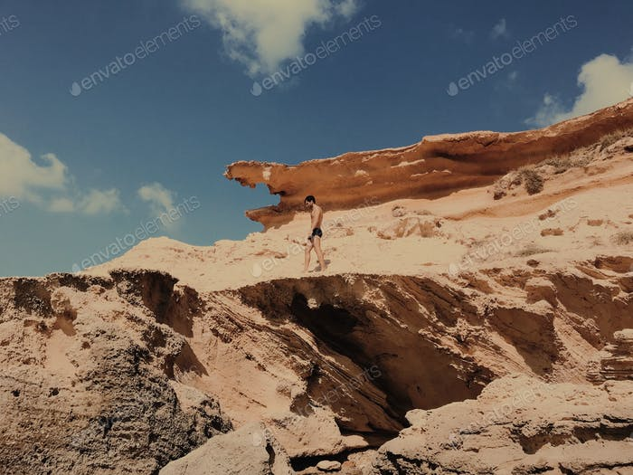 A man walking in swimwear on a erosioned rock.