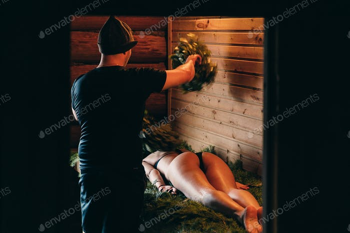 bath attendant soars a girl with a broom in a Russian bath