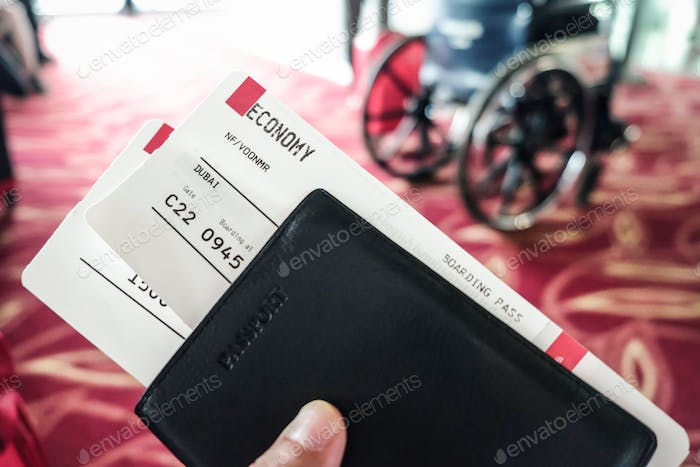 Closeup of boarding passes and passport at airport terminal boarding gate with a wheelchair in the