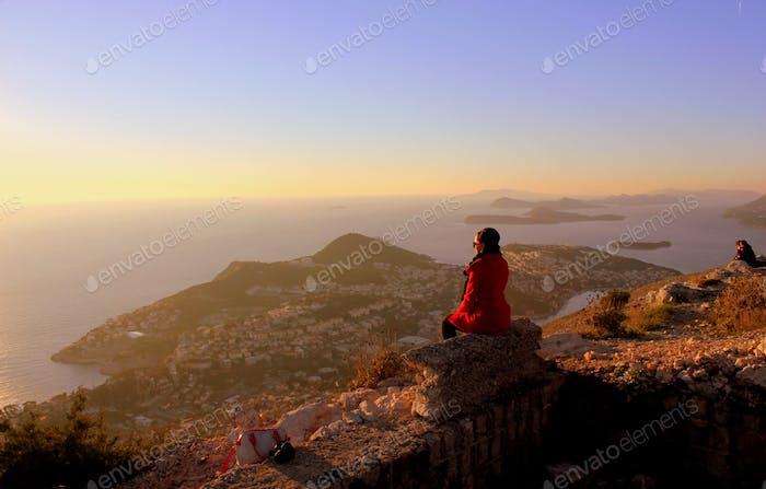 Stunning moment of female tourist enjoying sunset above Dubrovnik town at Adriatic sea of Croatia