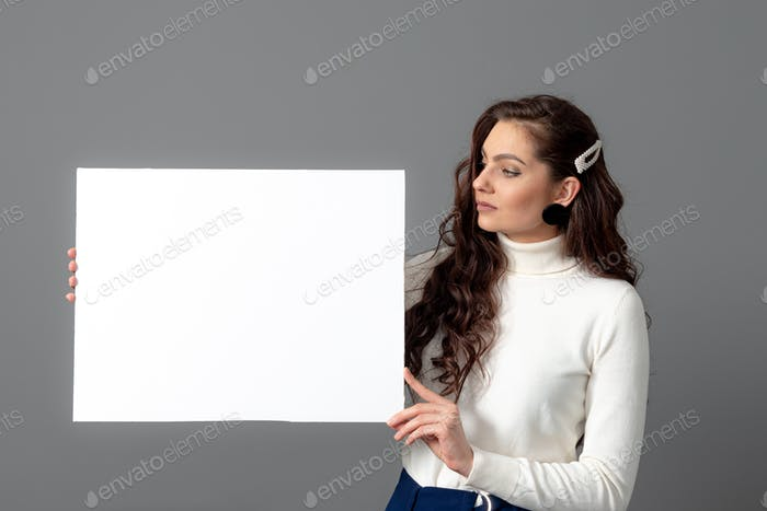 beautiful sensual woman with long curly hair shows a blank banner, isolated on gray, copy space