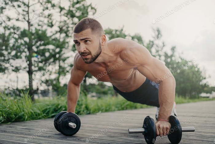 Muscular male bodybuilder does push up with barbells stands in plank pose