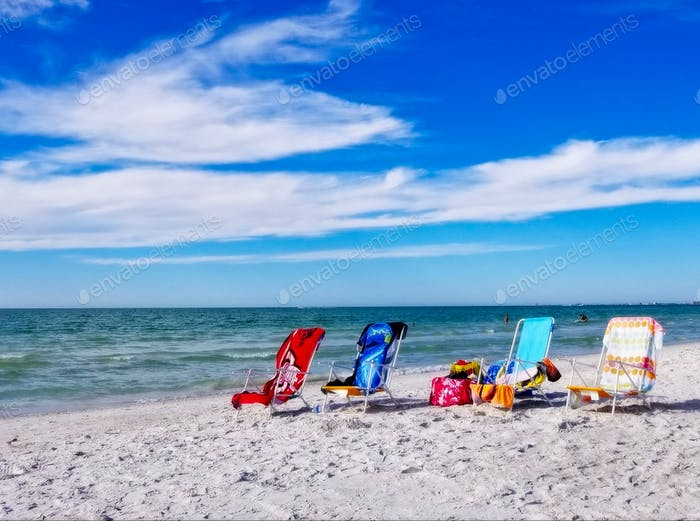 Empty beach chairs with a vibrant blue sky and sweeping clouds on Pass-a-Grille Beach, St