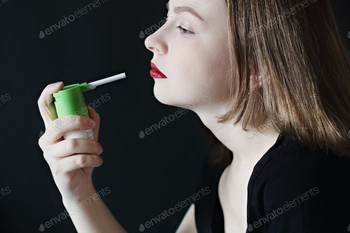 A young woman using a painkiller with an antiseptic spray to soften her throat, remove the pain.
