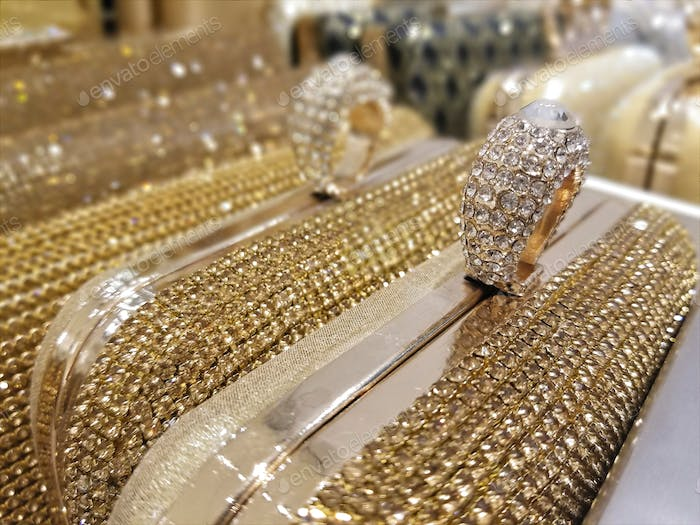 Sparkly clutch purses lined up on display in a store.