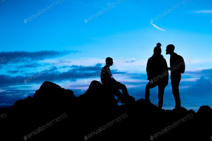 Silhouette of three hikers on a mountain top with blue sky and clouds - teamwork and achievement