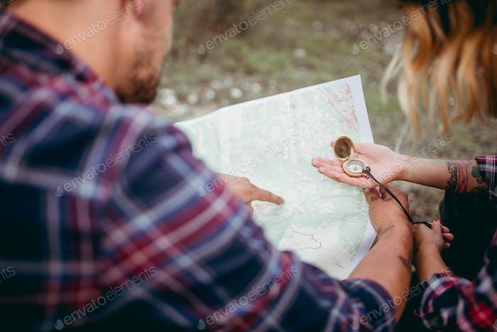 Paar plant eine Route auf der Karte mit einem Kompass
