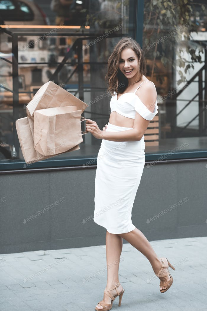 Stylish elegant girl walking on street holding paper bags with purchases over mall at background.