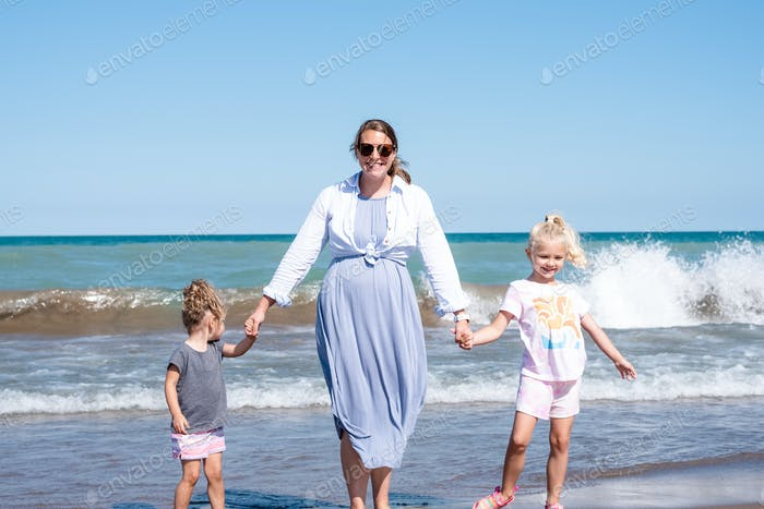 Light and airy portrait of happy young family walking hand in hand on the beach