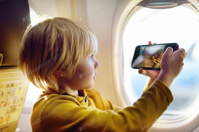 Thumbnail for Little boy is taking a shot view of airfield from illuminator plane by smartphone. Air travel