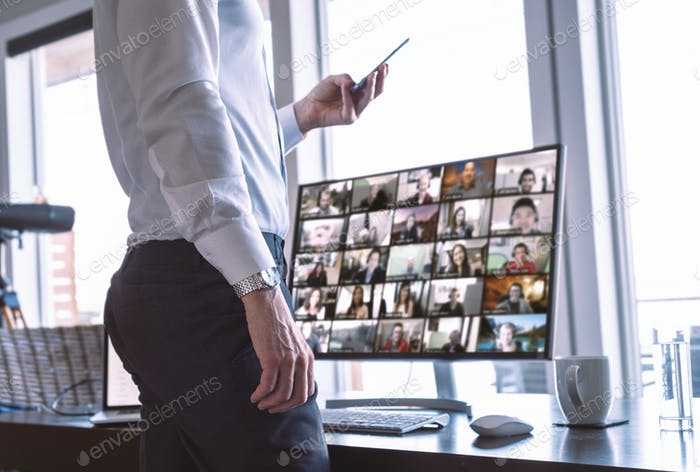 Businessman with his team on video chat computer screen, using phone