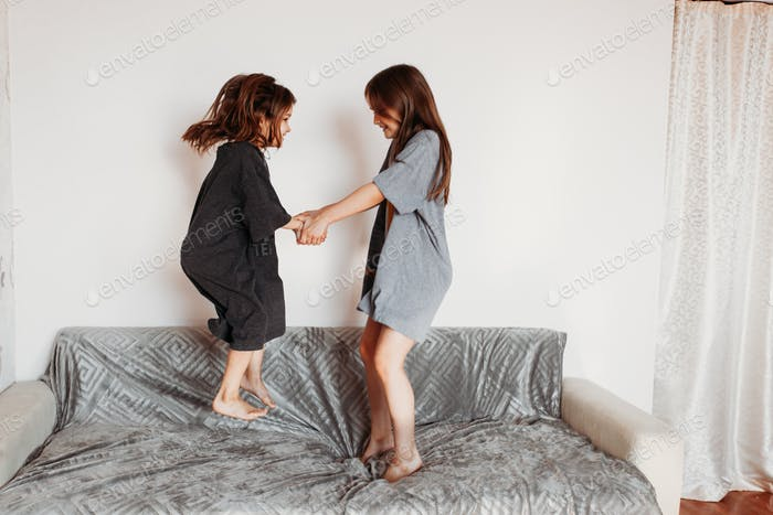 Two little girls, sisters playing at home, jumping on the couch, hugging, kissing each other, fighti