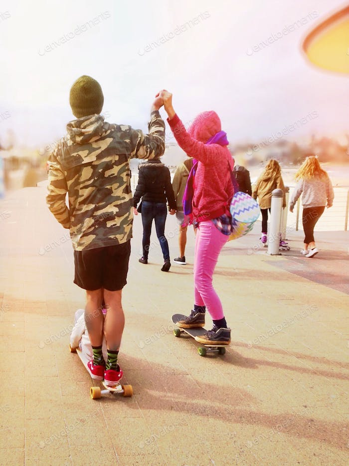 Happy couples- riding their skateboards together, holding hands up in the air, along the beachside
