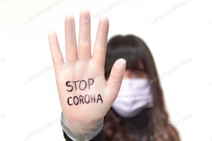 Woman's hand, stop corona, text, focus on foreground, covid, glove, mask.
