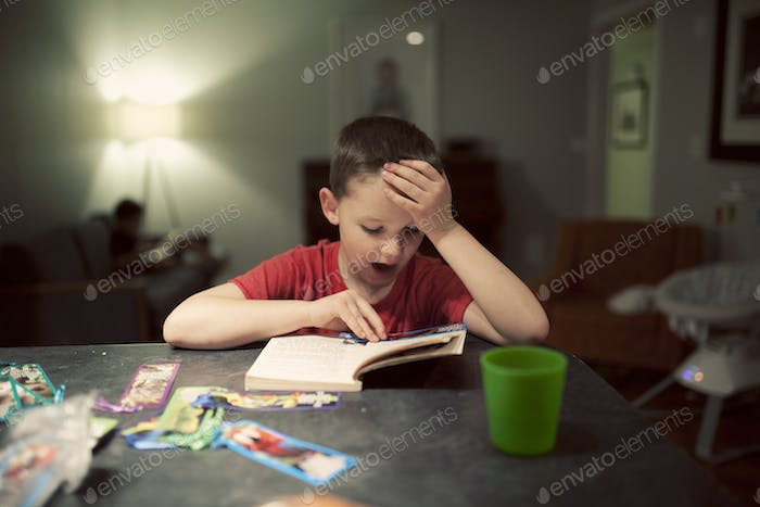 boy reading a book and using a bookmark to read the sentances