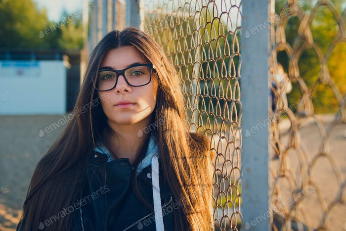 young woman long hair in glases posing outdoors looking at camera