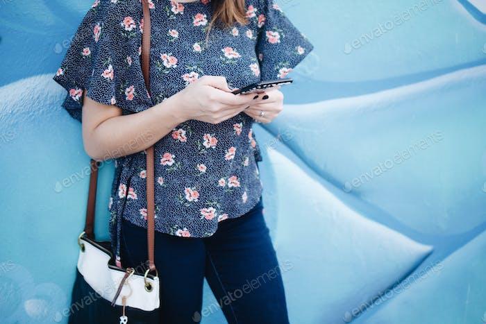 Woman against art mural using mobile