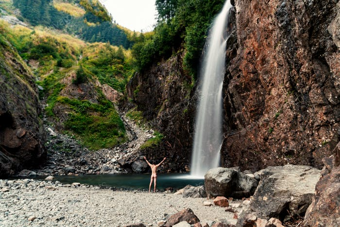 Long exposure waterfall in late afternoon light with rear view of nude man about to skinny dip with