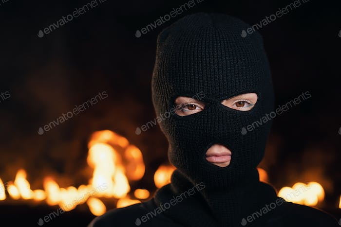 Portrait of young woman in black balaclava against backdrop of a blazing night fire