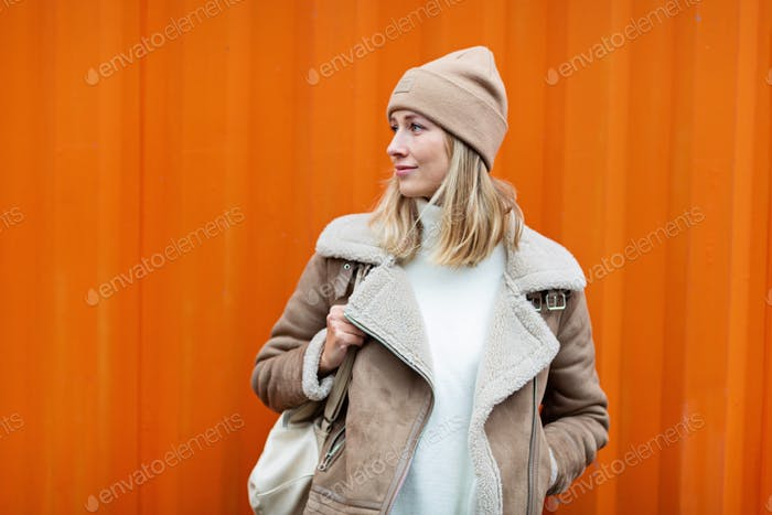 Beautiful young caucasian woman 20-30 years old in casual clothing near orange container wall