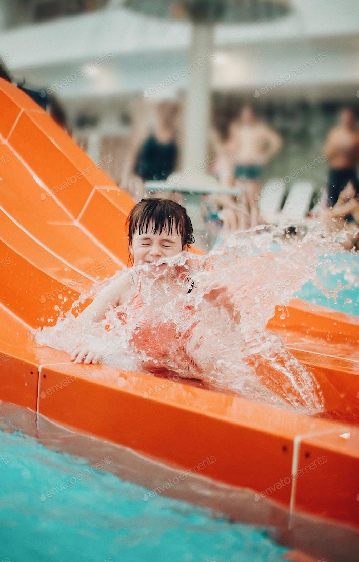 Little Girl slides in aquapark on a slide