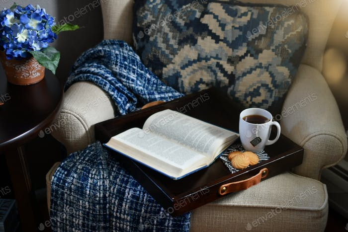 A cozy reading nook accented in blue with a tray of tea