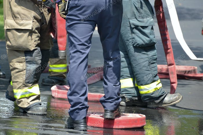 Firemen feet boots and fire hoses in water after fighting fire