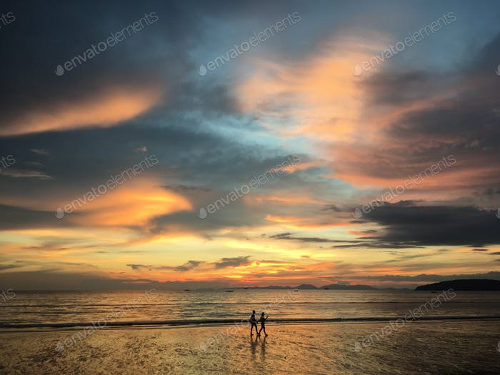 People walking on the beach at sunset.