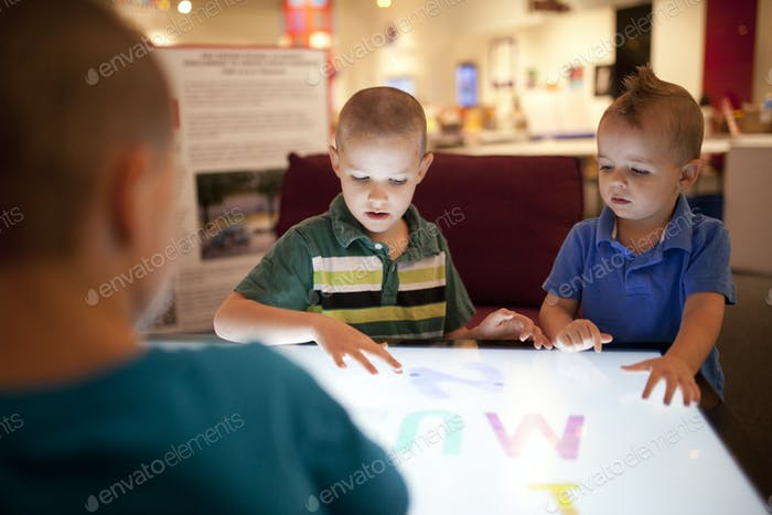 Jungs spielen auf einem riesigen Touchscreen-Microsoft-Oberflächengerät