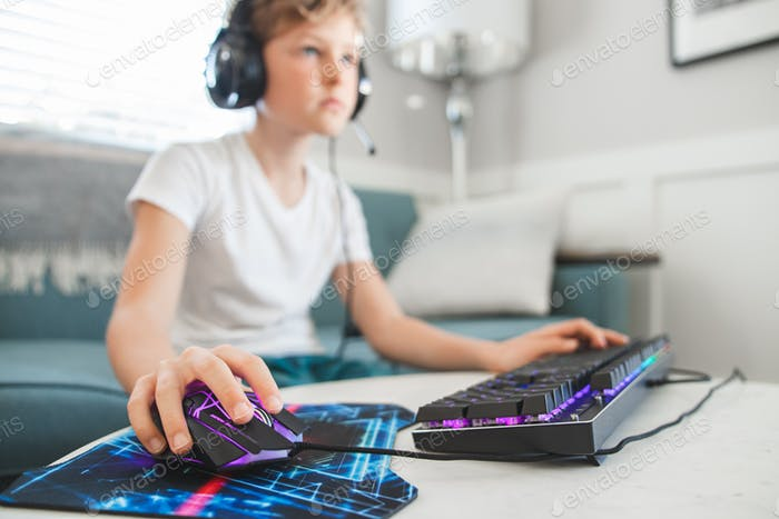 Boy on couch in brightly lit living room playing video games with a mouse and keyboard