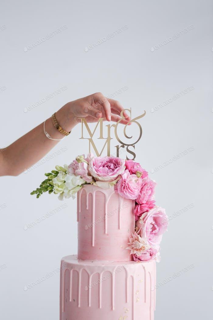 Rosafarbener Tropfkuchen mit frischen Blumen und goldfarbener MR&MRS-Aufsatz