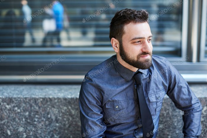 Young bearded Brazilian man relaxes on a bench in the Financial District in New York City